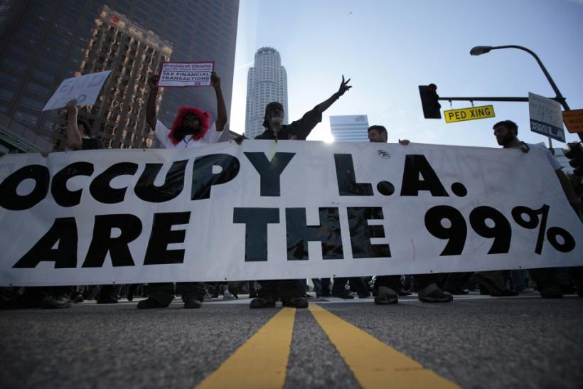 Protesters march with a large banner outside a Bank of America office at an Occupy LA protest in Los Angeles, California