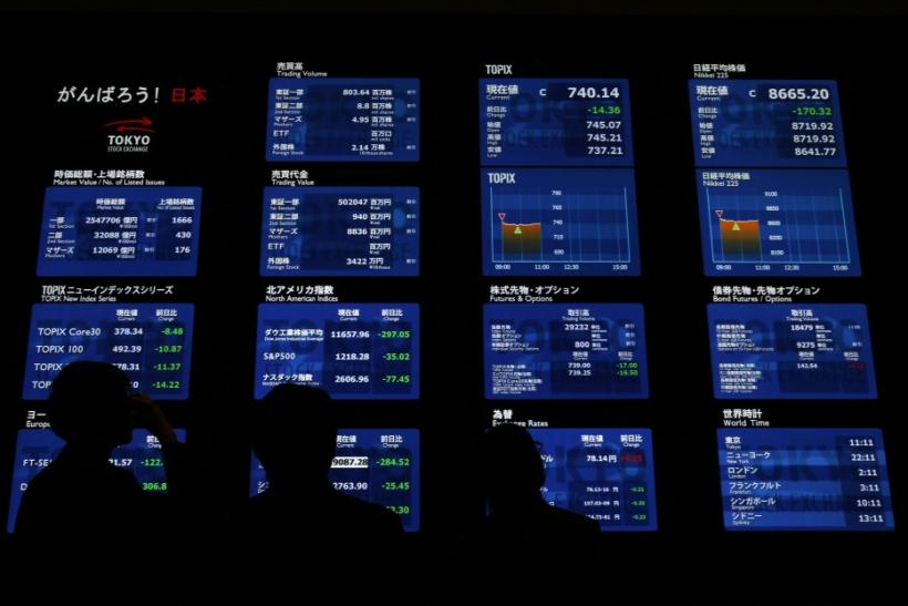 Visitors to the Tokyo Stock Exchange look at a monitor displaying various market indices in Tokyo