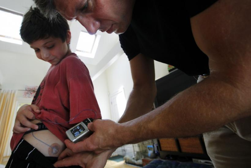 Ed Damiano (right) delivers insulin to his son David, at the family's home in Acton, Mass. Damiano is working on a bionic pancreas that will automatically control blood glucose in people with type 1 diabetes.