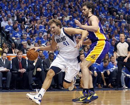 Dallas Mavericks power forward Dirk Nowitzki (L) drives the ball around Los Angeles Lakers power forward Pau Gasol in the first quarter during Game 3 of the NBA Western Conference semi-final basketball playoff in Dallas, Texas