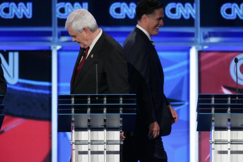 Former U.S. Speaker of the House Newt Gingrich, left, and former Massachusetts Gov. Mitt Romney are headed in different directions during a break in the CNN GOP National Security debate in Washington on Nov. 22.