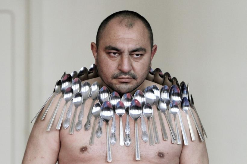 Etibar Elchyev poses with 50 metal spoons magnetized to his body during an attempt to break the Guinness World Record for