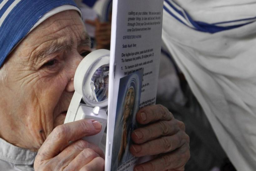 A Catholic nun from the Missionaries of Charity reads a pamphlet with the help of a magnifying glass during a prayer meeting in Kolkata