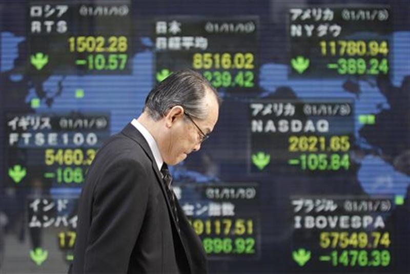 Man walks past an electronic board displaying falls in market indices from around the world outside a brokerage in Tokyo
