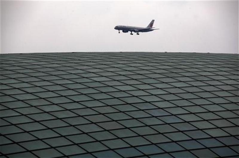 An Air China plane comes in to land over the roof of the railway station at Beijing's internationl airport