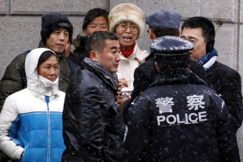 Supporters of Chinese rights activist Ni Yulan and her husband are pushed away by plain-clothes and uniformed police from the courthouse where activists are appearing on trial in Beijing