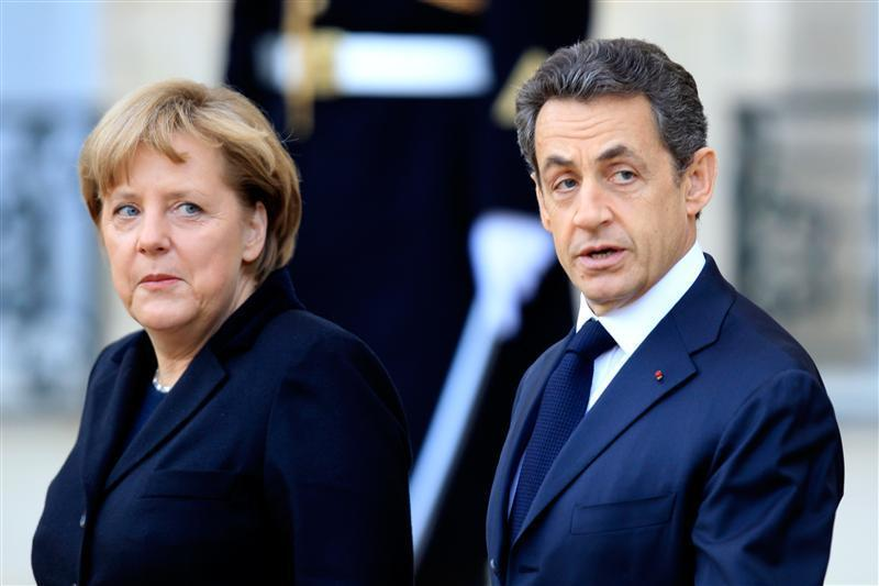 German Chancellor Merkel flanked by France's President Sarkozy leaves the Elysee Palace in Paris