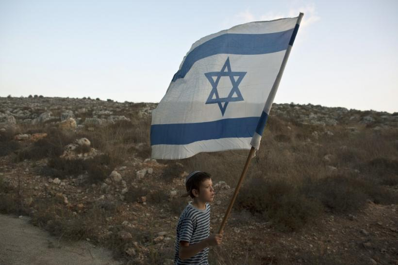 A Jewish youth holds an Israeli flag during a rally march outside the West Bank settlement of Itamar, near Nablus