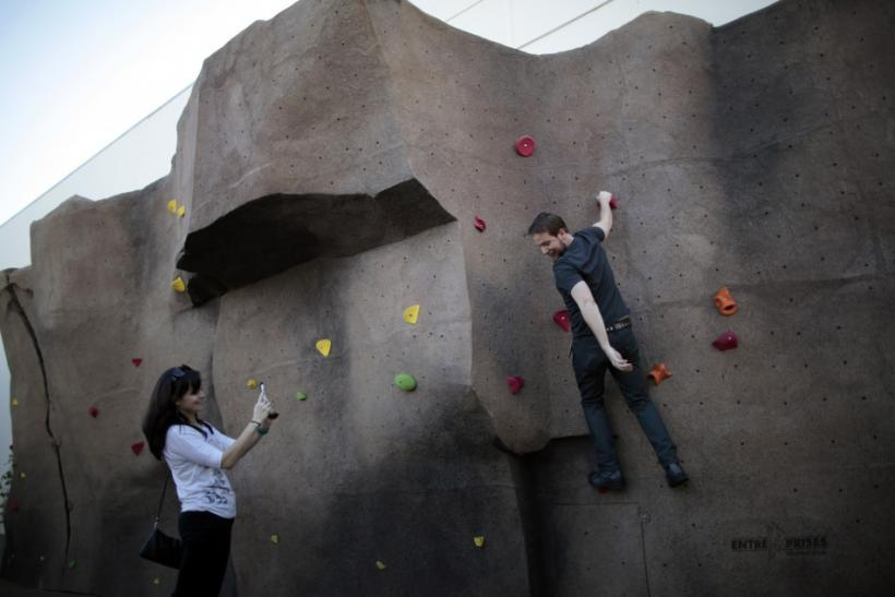 Systems Integrator Scott is photographed by his girlfriend Pynes as he tries out the rock climbing wall at the Google campus near Venice Beach, in Los Angeles