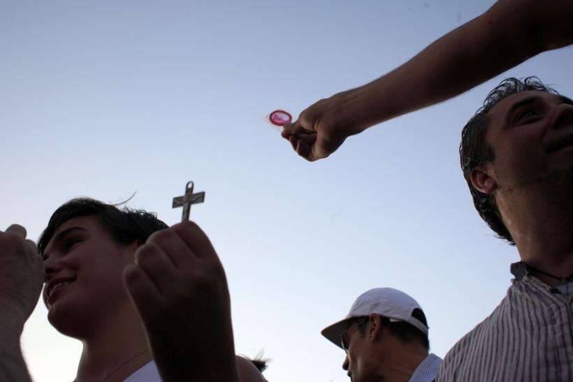 A protester shows a pilgrim a condom who in turn shows him a cross