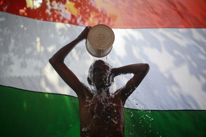 A man takes a bath outside his shanty in front of the Indian national flag in Dharavi, one of Asia's largest slums, in Mumbai
