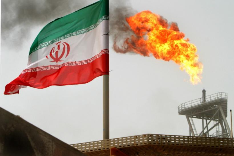 Gas flares from an oil-production platform in Persian Gulf at the Soroush oil fields with an Iranian flag in the foreground, about 776 miles south of the country's capital of Tehran