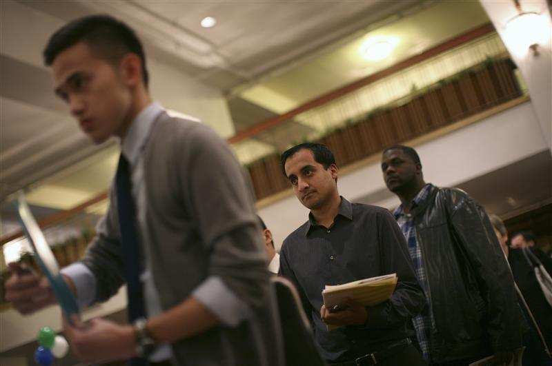 Job seekers stand in line to speak with an employer at a job fair in San Francisco