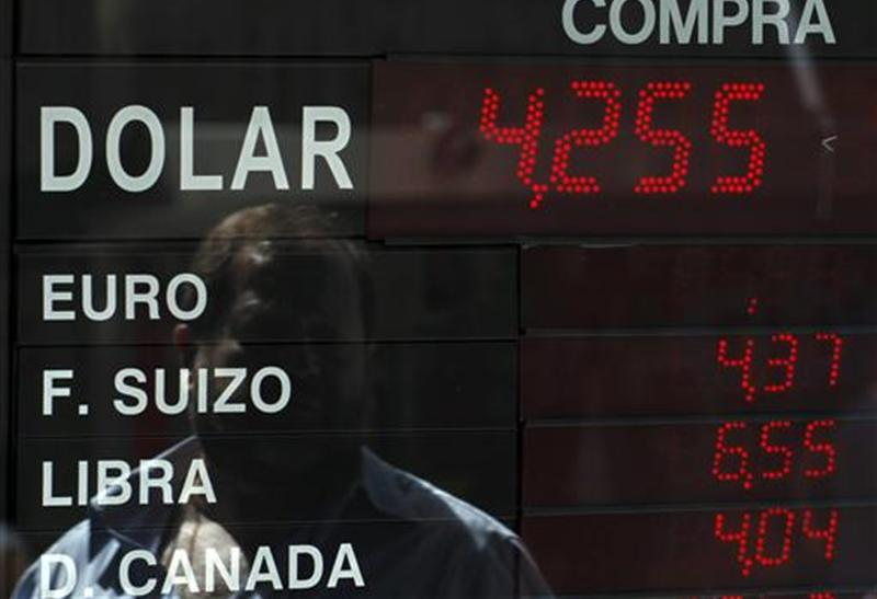 A man is reflected an electronic board showing currency exchange rates at a money exchange in Buenos Aires