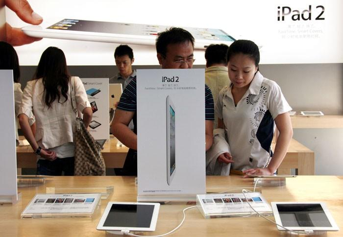 Customers look at various iPad 2 products during the China launch at an Apple Store in central Beijing