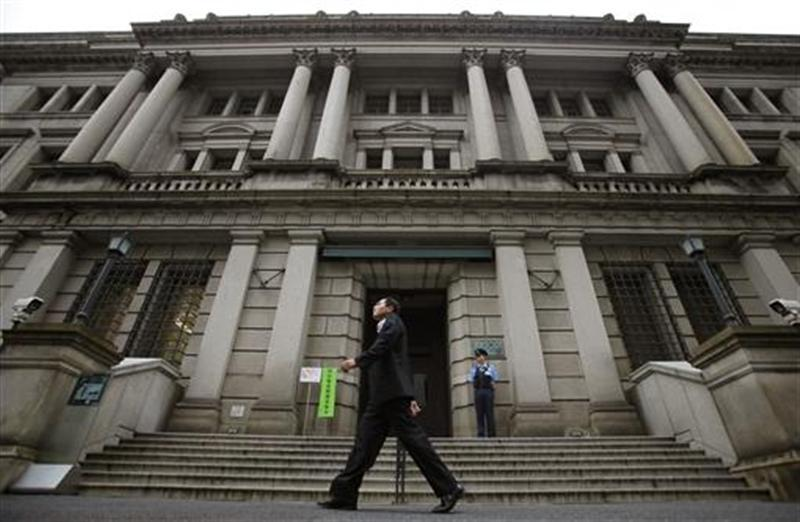 Man walks past Bank of Japan headquarters in Tokyo
