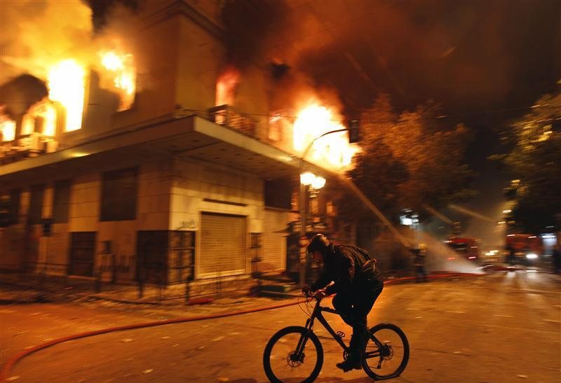A cyclist rides past a burning building during violent protests in central Athens