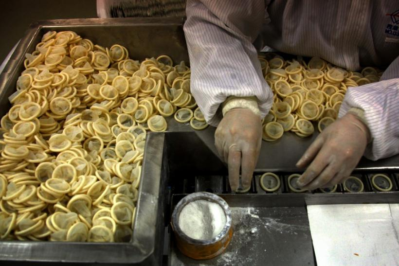 A worker places condoms onto a packaging belt at the Chinese condom manufacturer Safedom's factory in Zhaoyuan.