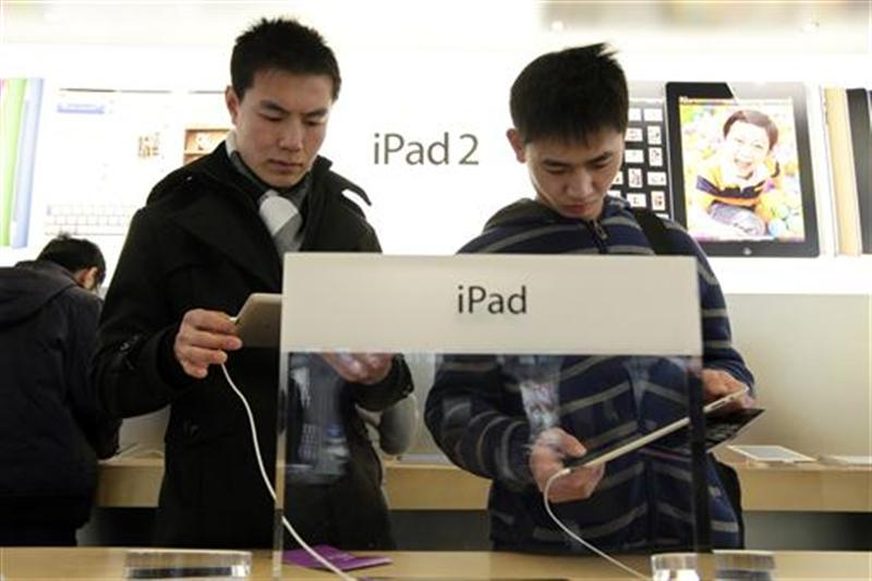 Customers test out Apple iPads in the company's flagship store in Beijing's Sanlitun Area