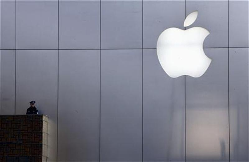 A policeman looks out from a balcony as the crowd is dispersed from the front of an Apple store in Beijing