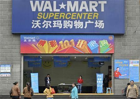 Employees stand in front of the gate to a Wal-Mart Supercenter in Chongqing municipality October 24, 2011. Wal-Mart stores in Chongqing reopened to surging crowds on Tuesday, two weeks after being shut down by local authorities for violating food and prod