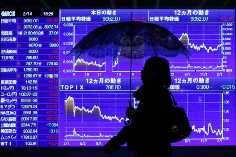 Woman walks past stock quotation board outside brokerage in Tokyo