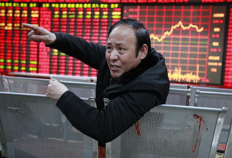 An investor gestures as he talks to a person in front of an electrical board showing stock information at a brokerage house in Huaibei