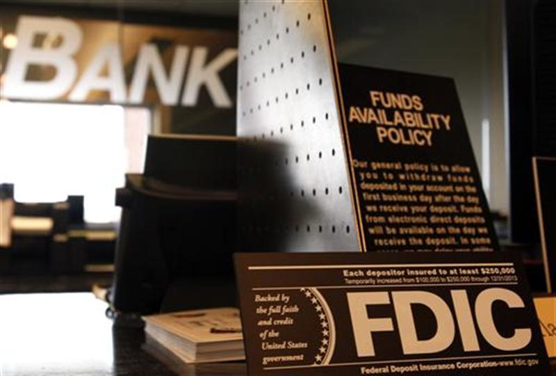 Signs explaining Federal Deposit Insurance Corporation (FDIC) and other banking policies are shown on the counter of a bank in Westminster