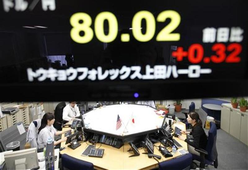 Foreign exchange dealers are seen beneath an electronic board displaying the Japanese Yen's exchange rate against the U.S. dollar, in Tokyo