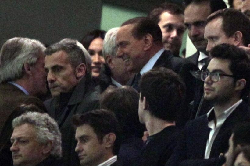 Former Italian Prime Minister Silvio Berlusconi (C) smiles as he arrives before the Italian Serie A soccer match between AC Milan and Juventus at the San Siro stadium in Milan February 25, 2012.