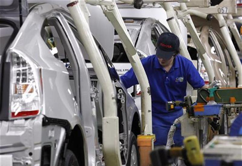 "An employee works on an assembly line of Toyota Motor Corp's hybrid car ""Prius"" at Tsutsumi plant in Toyota Dec. 9 2011"