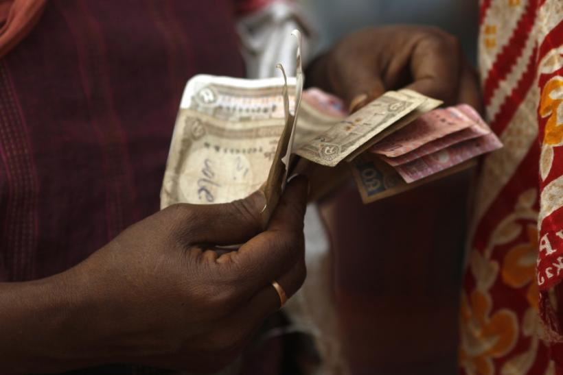 A woman counts out Bangladeshi banknotes in Dhaka.