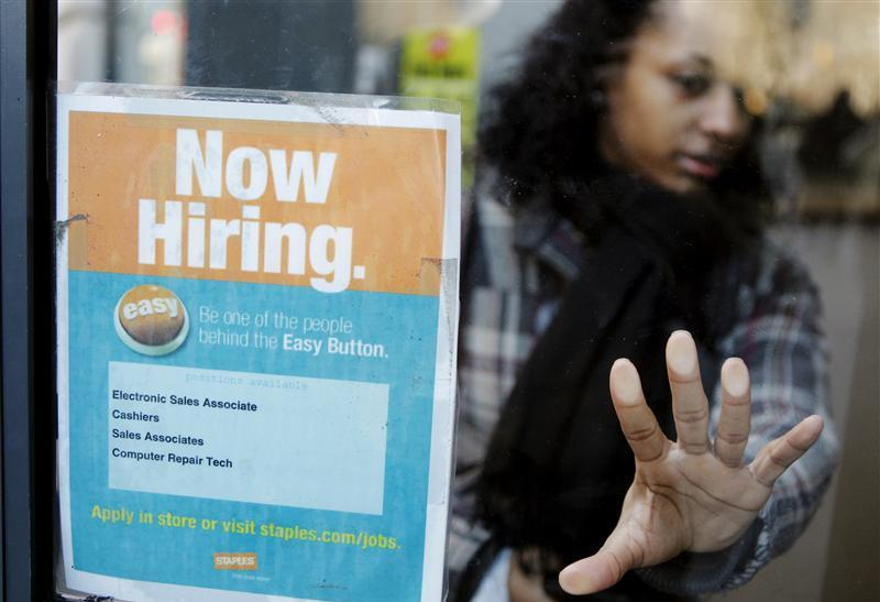 "A woman opens a glass door with a ""Now Hiring"" sign on it as she enters a Staples store in New York"