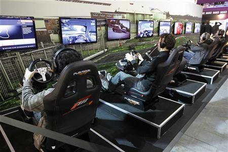 Visitors play a car racing video game during a visit at the Paris Games Week show in Paris October 21, 2011. The Paris Games Week will run from October 21 to October 25.