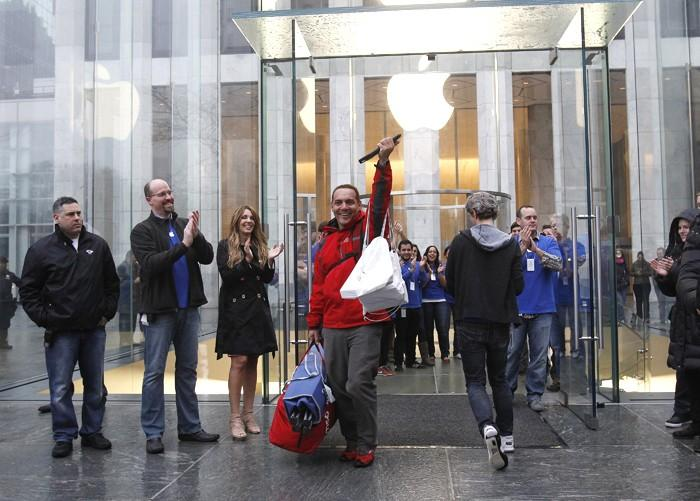 A man raises Apple's new iPad after purchasing it in New York