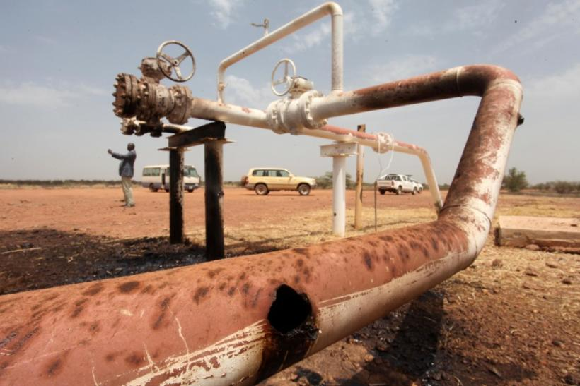 Oil spills onto the ground from an oil well head strafed by shrapnel from a bomb dropped by fighter jets at the El Nar oil field in South Sudan's Unity State