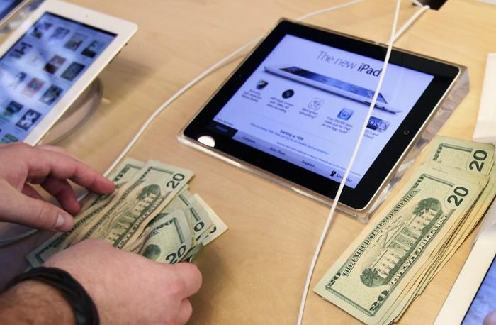 An Apple employee counts money as a customer purchases Apple's new iPad at the 5th Avenue Apple Store in New York