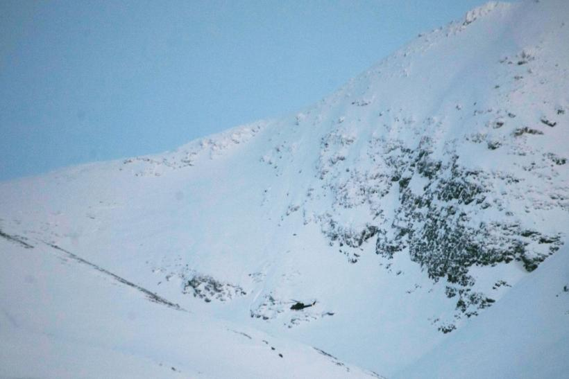 A helicopter searches a mountain area where an avalanche is reported, in Kafjord