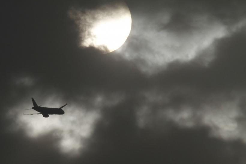 A passenger aircraft is silhouetted against the rising sun after its take-off at the airport in New Delhi