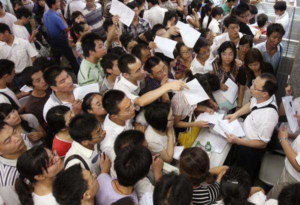 Jobseekers pass their resumes to representatives from Foxconn Technology Group at a job fair in Zhengzhou