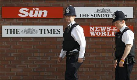 Police officers walk outside an entrance to News International in London in this July 10, 2011 file photo.