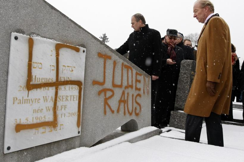 "France's Interior Minister Hortefeux walks next to a tombstone desecrated by vandals with Nazi swastikas and the Slogan ""Jews out"", in the Jewish Cemetery of Cronenbourg"