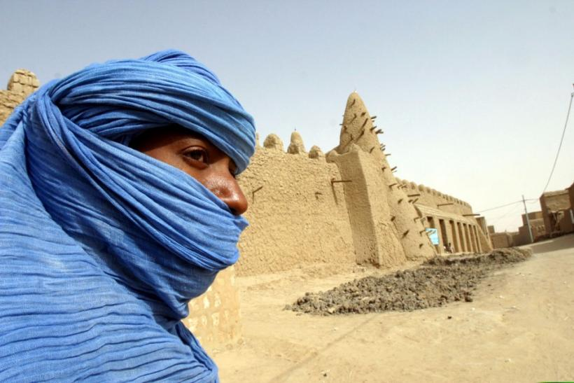 A Tuareg nomad stands near the 13th century mosque at Timbuktu, Mali.