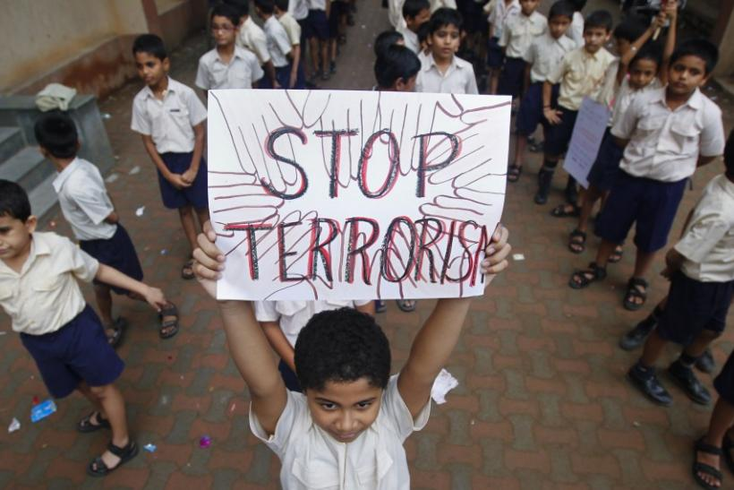 A student lifts a placard as he and others line up to take part in a march for peace in Mumbai