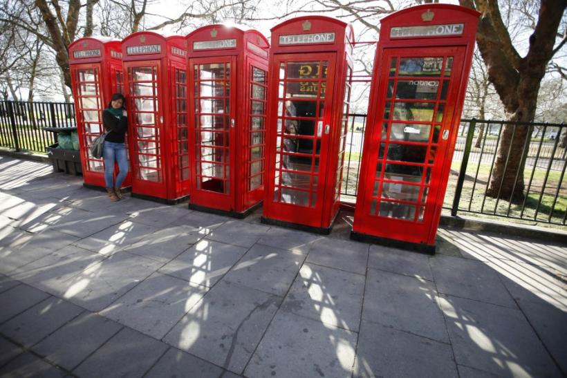 A tourist poses for a photo next to four telephone boxes next to Hyde Park, in central London