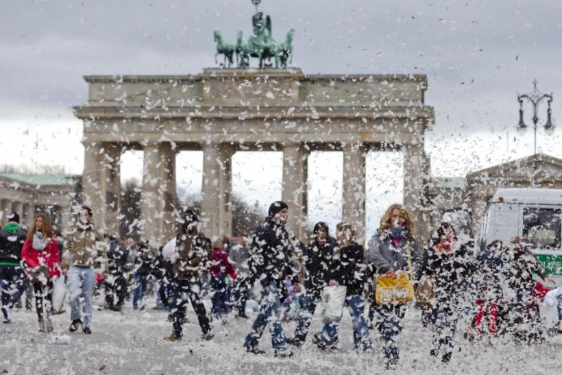People walk near Brandenburg Gate as feathers fill air after pillow fight flashmob in Berlin