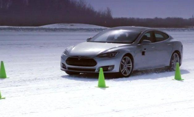 A Tesla Model S drives in the snow.