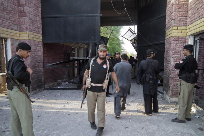 Policemen gather near a damaged jail gate after inmates escaped from the prison in the town of Bannu Pakistan
