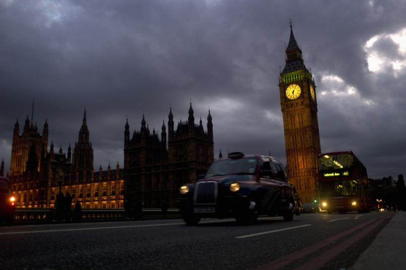 A bus and taxi pass Big Ben on Westminster Bridge in London