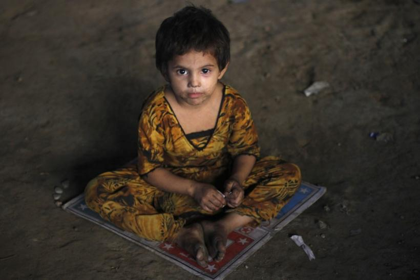 A three-year-old homeless Hindu girl, is photographed as she sits on a board game while taking shelter under a bridge in Karachi